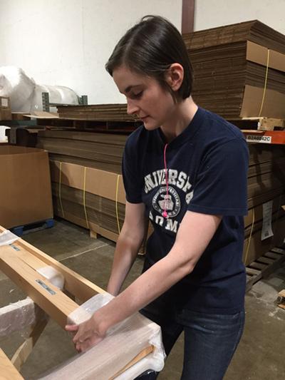 Leah packs a natural platform bed for shipment