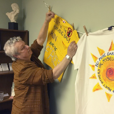 Sarah Ellis hangs inspirational t-shirts in her office at the Shelter for Help in Emergency