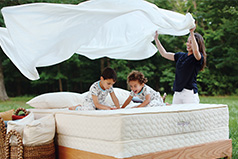 Family playing on an organic mattress from Savvy Rest