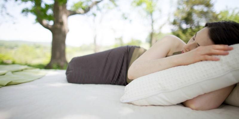 Woman sleeping on a Savvy Rest organic mattress