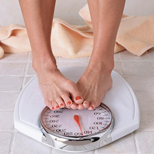 Lady weighing herself on a scale