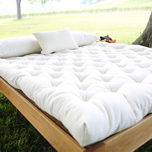 Savvy Rest's Pastoral organic wool mattress resting on the natural platform bed