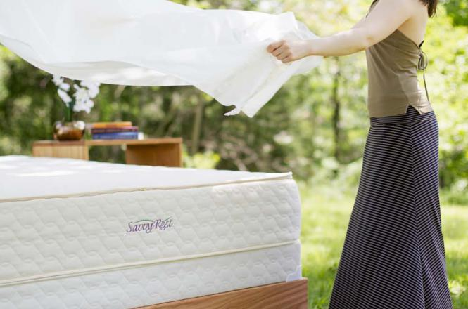 Lady putting cotton sheets on her Savvy Rest mattress