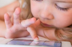 Child using a smartphone in bed